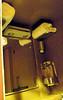 Mirror, overhead towel rack and light fixture, water dispenser in water closet/toilet.