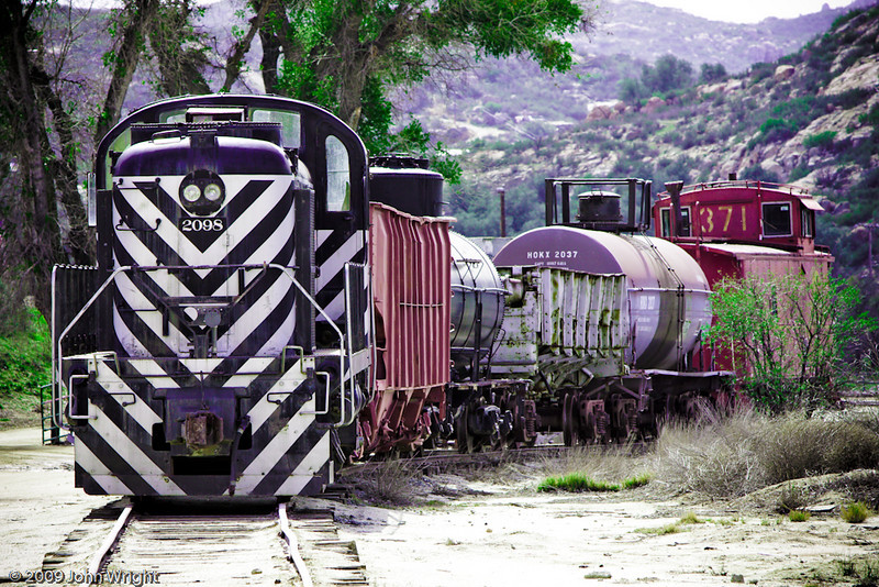 Small consist of two hopper cars, two tanks and a caboose, led by SF 2098.
