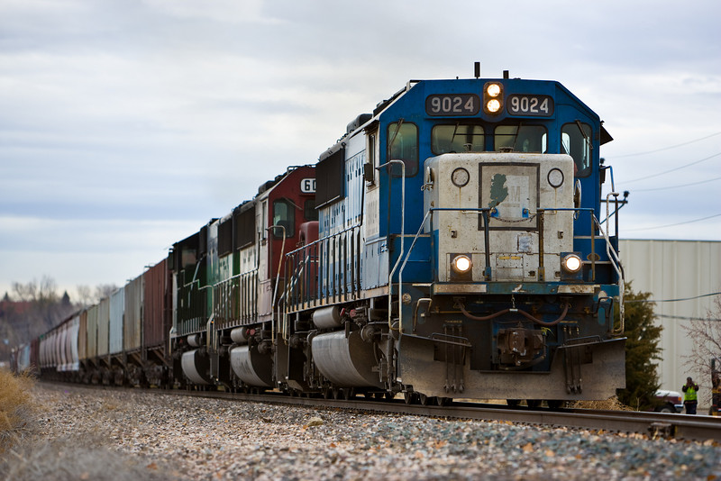 A colorful consist, a trio of SD-60s heading south through Longmont, CO. EMD 9024, SOO (now CEFX) 6008 and wide cab BNSF 9260 on November 17, 2007. Who is the guy in the green vest and why is he there?