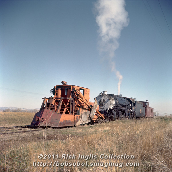 """Slide No. 783. C&S 809 and flanger 99271 stopped """"just north of Fossil Creek."""" A crew member examines something near the feedwater heater pump."""