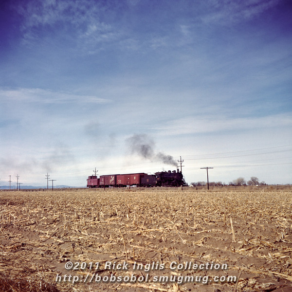 Slide No. 154. C&S 620 pulls two cars and caboose 10583 east through northern Colorado.