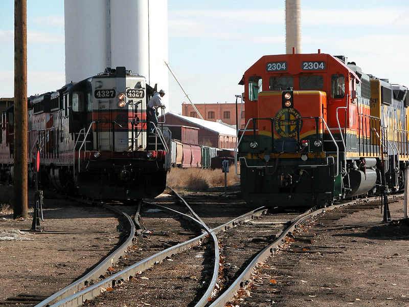 "A meet in GW's Loveland yard between the BN local and a pair of GW SD9s making up the last ""passenger"" train headed for Johnstown. GW's passenger cars were headed for the North Alabama Railroad Museum on November 14, 2002. Only people who helped ready the cars for shipment were told of this special train, and were permitted to ride one-way. Unfortunately, I had an employer waiting for me!"
