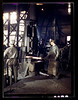 Working with a small steam drop hammer at the blacksmith shop in the Santa Fe R.R. shops, Topeka, Kansas, March 1943