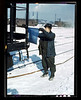 John Paulinski, car inspector, blue flagging a train for inspection, at Corwith yard, Santa Fe RR trip, Chicago, Ill. March 1943
