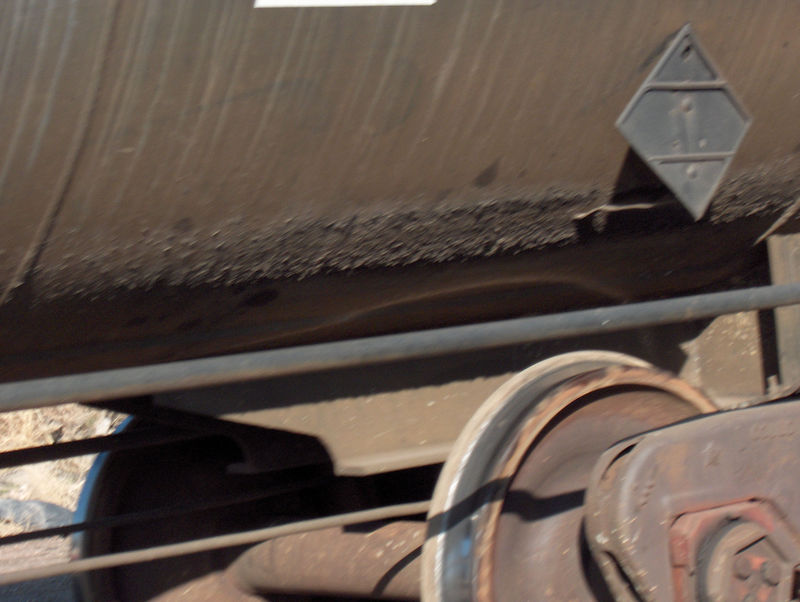 There is actually a texture to the grime that the wheels kicked up on the bottom of this tank car. BN, Loveland CO.