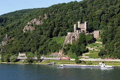 Transport in the Rhine Valley. A 101 heads an Intercity service on the west bank underneath Rheinstein Castle as a barge heads up stream. Wednesday 5th July 2017.