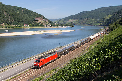 DB's 185 148 passes Assmannhausen on the east bank with a southbound mixed freight. Reichenstein Castle towers over the west bank. Wednesday 5th July 2017.