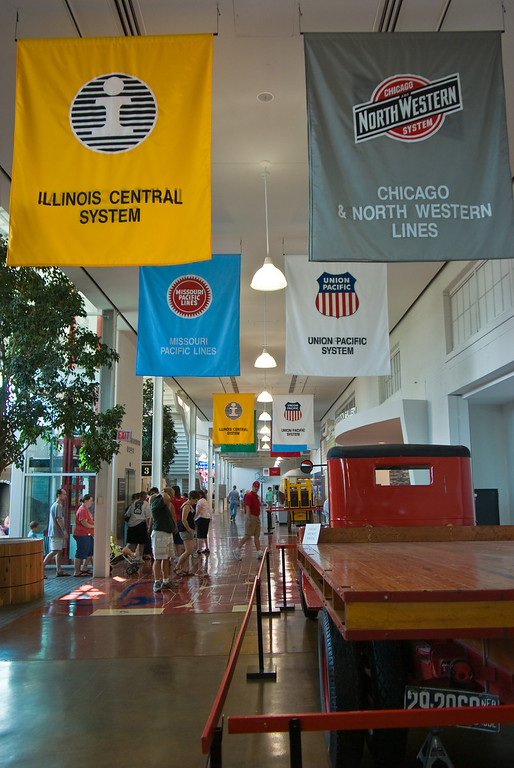 Banners with logos of various railroads that operated out of Union Station hang from the ceiling.