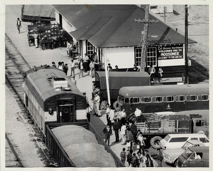 Train time in Moosonee, picture published in the Chicago Sun Times of 1974 May 5. Multiple baggage carts, military bus, one FP7 locomotive. Ontario Northland Railway train arriving in Moosonee, Ontario.