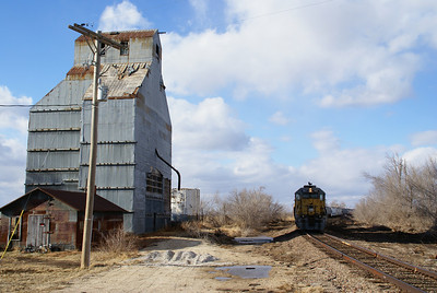 K & O train parked beside abandoned elevator at Elmer, KS