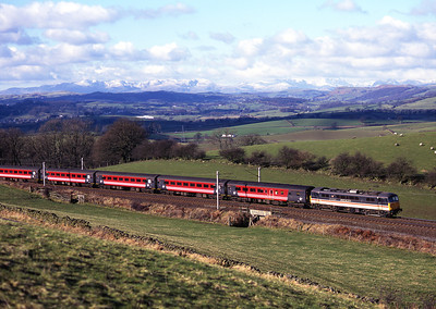 """86207 """"City of Lichfield"""" heads north at Hayfell with the Lake District mountains in the background 19/2/00."""