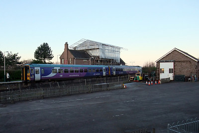 A pair of Northern Rail Class 153s call at Ravenglass on a Saturday morning - note the scaffolding around the roof of the Ratty Arms, repairing the fire damage, 12/12/09.