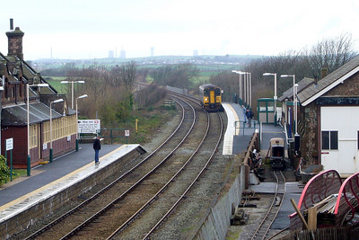 A Class 153 DMU arrives heading south at Ravenglass, with the chimneys of Calder Hall and Windscale Pile at Sellafield visible in the distance, 24/02/07.