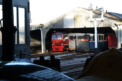 A different view - Douglas Ferreira pokes out of the carriage shed as Northern Rock and River Mite rest in the engine shed at Ravenglass, 11/02/08.