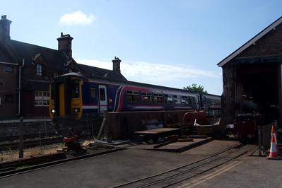 156420 La'al Ratty Ravenglass & Eskdale Railway departs Ravenglass, passing River Mite outside the workshop, 06/06/08.
