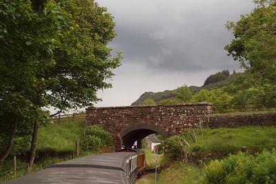 Douglas Ferreira approaches Muncaster Mill (visible through the A595 road bridge) as a storm brews over Muncaster Fell. 10/06/11.