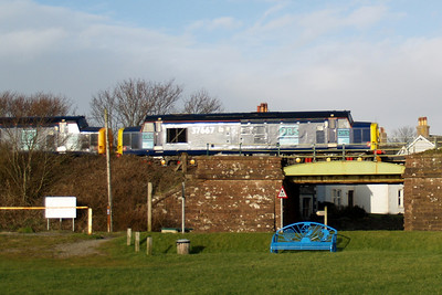 37667 and 37688 Kingmoor TMD cross the bridge which carries the Cumbrian Coast Line over Ravenglass Main Street, 08/03/08.