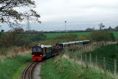 Douglas Ferreira approaches Ravenglass, passing Raven Villa, with the wind turbine at Thornflatt farm, Carlton, on the horizon, 10/10/09.