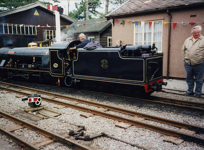 Peter van Zeller backs down River Esk onto her train at Ravenglass as long-time volunteer the late Dai Pickup looks on.