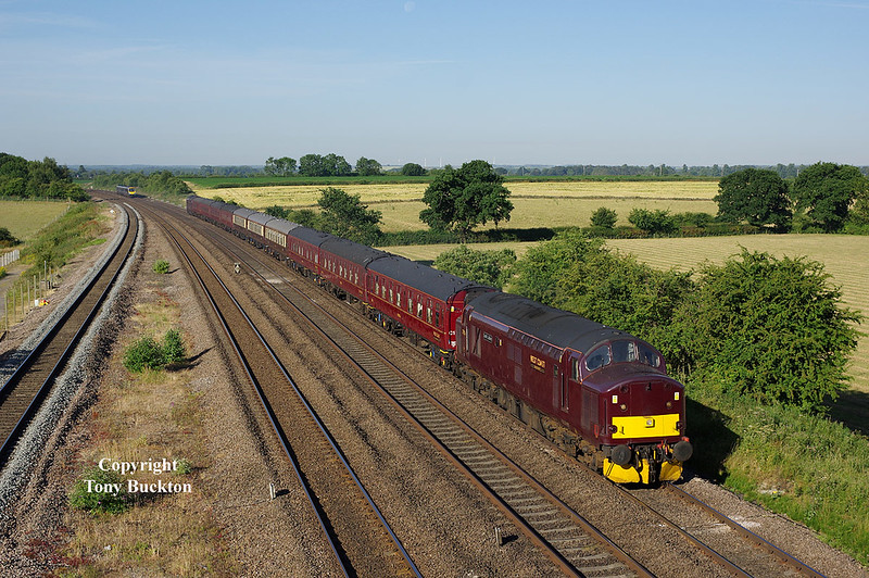 37516 leads the 5Z45 02:30 Carnfoth Steamtown - York empty coaching stock through Bolton Percy at 07:45 on Monday 2nd July 2018. The stock would later form the Dalesman charter to Carlisle led by 37669 which is attached to the rear.<br /> Note that the moon can be made out at the very top centre of the shot!