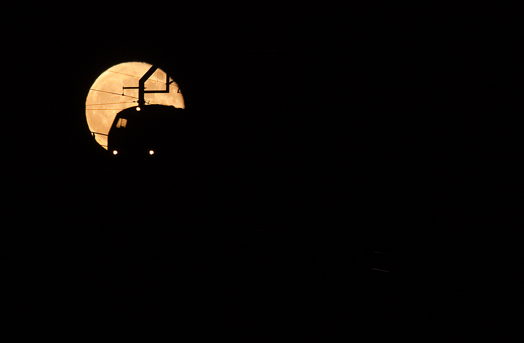 <b>13-Dec-2008</b>  A full moon on a clear, cold night made me go out and experiment a little. As luck would have it the last 225-hauled train into Belgium showed up at the right time. Here it is silhouetted against the largest full moon of the year.