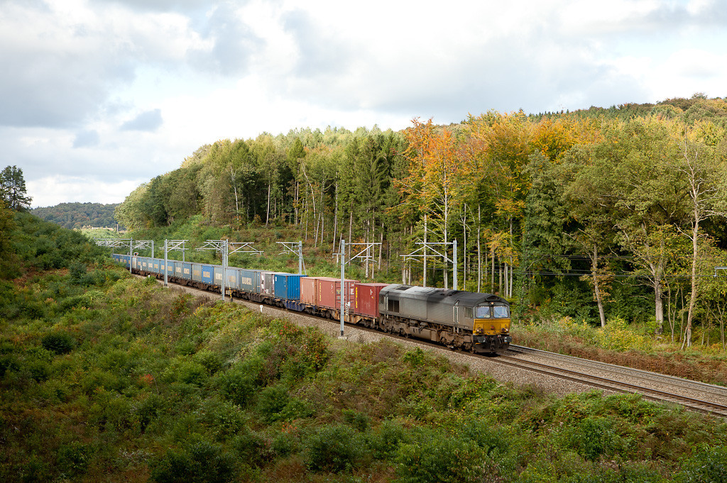 <b>5-Oct-2010</b>  The nice weather beckoned me to leave the office early and head out to the forest to check the fall colors. Of course it clouded up merely seconds before this plain-vanilla 66 came up from Aachen with the loaded Bulkhaul train. Every now and then there are some other boxes added to the consist as is the case on the first three platforms here.  <i>An unidentified DLC 66 with the westbound Bulkhaul train passes the Rue d'Aix in Moresnet.</i>