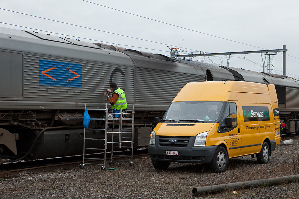 <b>29-Dec-2009</b>  Three of Crossrail's Class 66 units - PB12, PB13, and PB19 - lost their old beat-up DLC decals in Montzen today. A poor soul from RailServiceNet equipped with a hot-air gun powered by a portable generator scraped away at them relentlessly in the sub-zero temps.  Whether they will be replaced with Crossrail decals, or whether the engines remain gray (or indeed are being returned to CBRail) is anybody's guess right now. Time will tell.  <i>Postscript: they were returned to the lessor.</i>