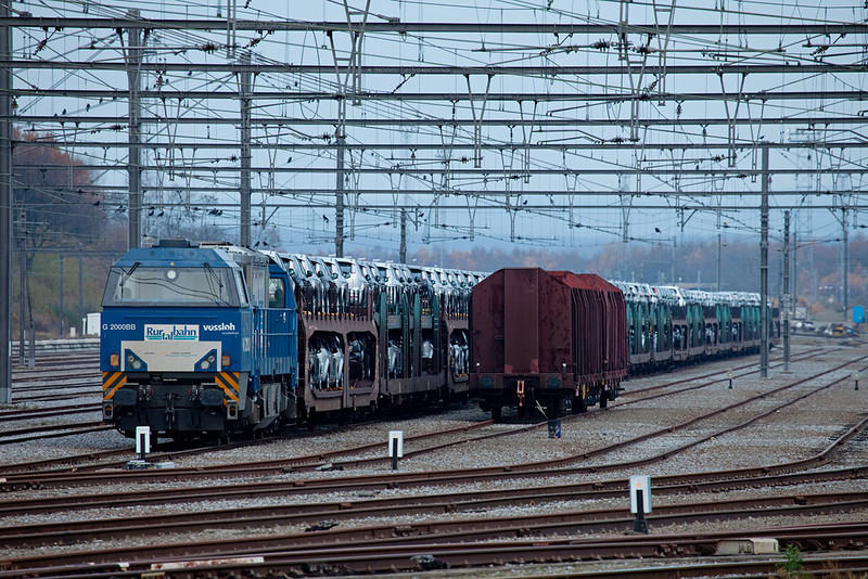 "<b>21-Nov-2009</b>  Montzen yard continues to see some activity 11 months after B-Cargo pulled out. The private guys still make use of track capacity to store trains, as evidenced here by Trainsport (Rurtalbahn) with a Ford train with their blue G2000 V203 for power.  TSP seems to always have a few engines around, their class 66 and another G2000 with a sugar train were present as well. They usually congregate around tower 15 in the middle of the complex, while DLC parks their 66s near their ""gas station"" on the south side near the customs shed.  <i>Rurtalbahn/Trainsport G2000 V203 with Ford autotrain in Montzen.</i>"