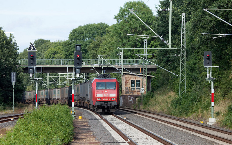 <b>23-Jul-2009</b>  This week freight traffic is diverted from the main traffic artery between Aachen and Cologne due to construction curfews. The trains continue north through Cologne, west to Grevenbroich between Cologne and Düsseldorf, and then head due south along the 485 to Aachen.  This is a rare opportunity to photograph more than the usual trickle of freight traffic on this line. Here one of the signature trains, the Ambrogio intermodal to Muizen/B, passes the abandoned tower Ln in Lindern, about 30 km north of Aachen. This station was converted from manual block with semaphores only last year, 2008.  <i>145 080 leads the Ambrogio intermodal TEC 40098 (Gallarate - Muizen) through Lindern.</i>