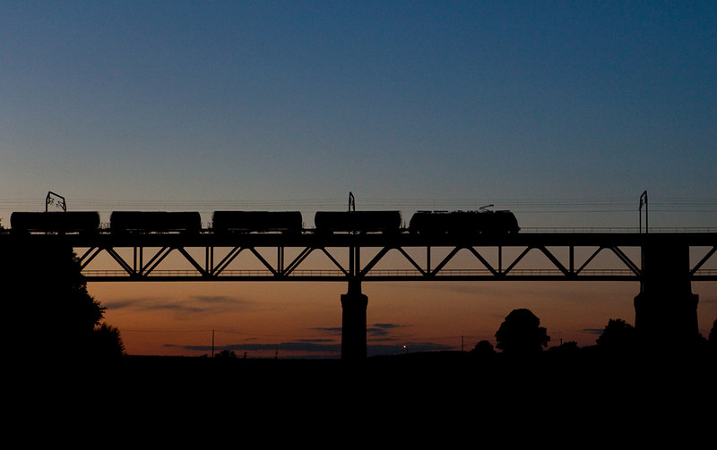 <b>19-Jun-2009</b>  Home for a change. As we approach midsummer, the sun sets far enough north for the sunset to light up the skies behind the Moresnet Viaduct. An eastbound tank car train is led by one of the now-ubiquitous class 28 electrics.  <i>Class 28 with tank car train at sunset.</i>