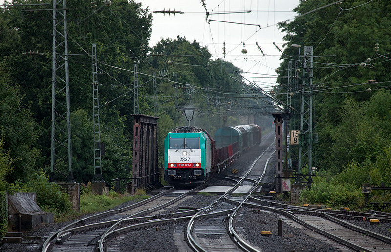 <b>24-Jul-2009</b>  The diverted freights are unusual enough to warrant another outing. Friday's weather ran the gamut from torrential rains to bright sunshine and blue skies and back within 10 minutes.  Shortly after a downpour this Traxx brings a steel train down the steep incline from Kohlscheid into Herzogenrath. The catenary is still dripping wet as the pantograph creates a nice misty swirl.  Even bad weather has its advantages, it doesn't always have to be sun-over-your-shoulder. A platform shed that keeps you nice and dry is an asset, though...  <i>Cobra 2837 on the FE 44565 (Kinkempois - Gremberg) approaches Herzogenrath northbound.</i>