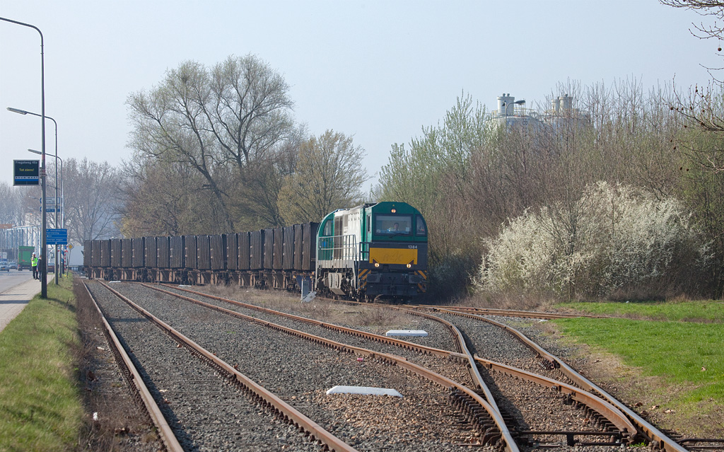 <b>3-Apr-2009</b>  I have wanted to follow one of the ACTS trash trains in the Limburg region of the Netherlands for quite some time, and on the 3rd of April I finally did. ACTS serves a number of transloads, including one in the Beatrixhaven industrial estate north of Maastricht.  Here we see rented Vossloh G2000 1384 (with the odd asymmetrical cab) after having pulled the Essent facility and backed the train down to the little yard. As soon as the brakeman has walked back to the engine they will pull out, run down the main south into Maastricht, pick up the other half of their train (from Haanrade) left there, and run north to Wijlster.  This G2000 will be returned to Vossloh on the 4th. ACTS at this time receives a total of 6 G2000s to pinch-hit for their fleet of G1206s which are having a/c units installed at Vossloh in Moers. Good move; as can be seen by the blooming bush, temperatures are on the rise. 24 degrees C and counting...  <i>Vossloh 1384 with the ACTS trash train 50101 (Beatrixhaven - Maastricht) in Weert.</i>