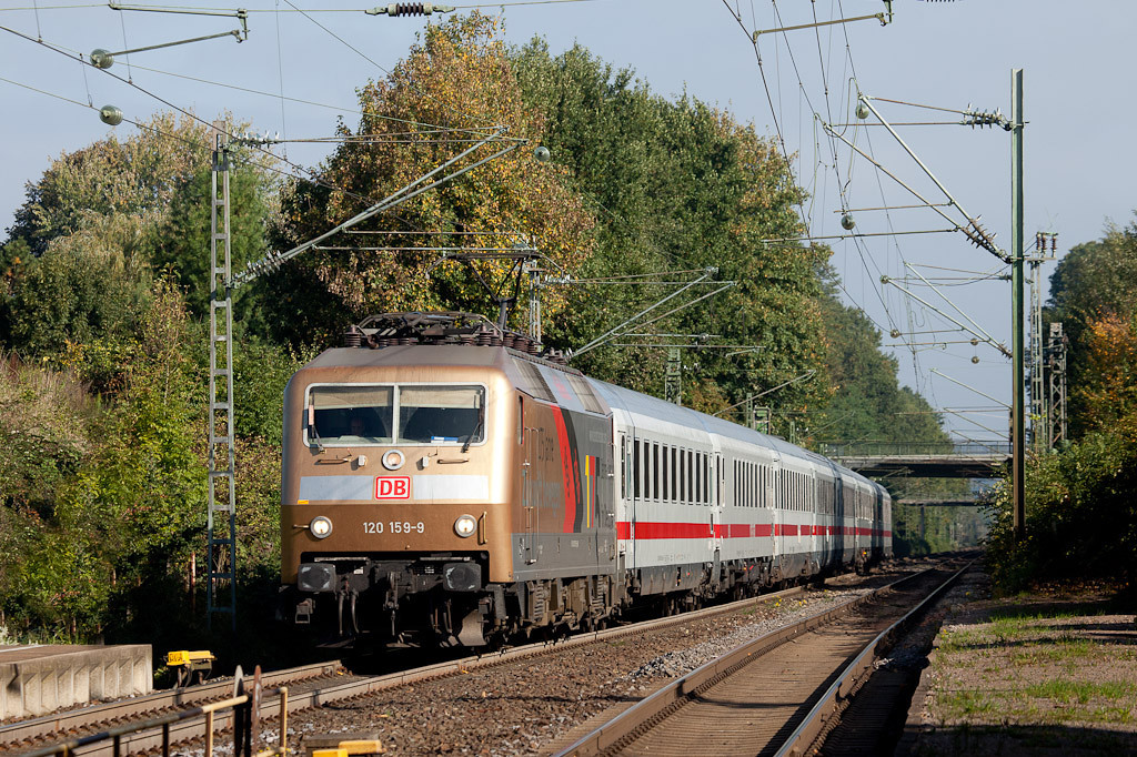 <b>8-Oct-2010</b>  This Friday one of DB's special-liveried engines was booked for the IC 1918 (Aachen - Berlin). The rack is on the south end which means it pushes the train all the way; not very useful for photography.  However, the train arrives as an empty stock move about half an hour before departure, with the engine leading into the sun.  Here 120 159, wearing silver and gold commemorating 175 years of railroads in Germany, passes some fall color 10 minutes north of Aachen. Hm. I remember the 150 year festivities and the stickers they pasted onto engines back then - must be getting old...  <i>120 159 on empty stock move Lr 78532 (Dortmund Bbf  - Aachen Hbf) for the IC 1918 heads southbound through Kohlscheid.</i>