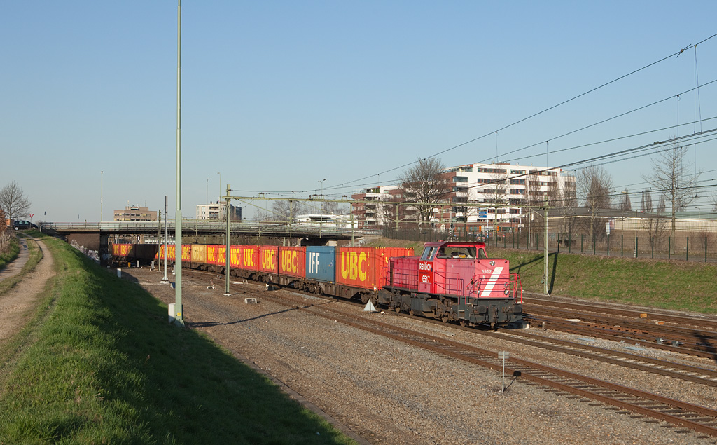 <b>20-Mar-2009</b>  63084 is always an exceedingly colorful train, courtesy of the UBC and IFF bulktainers it carries to the giant DSM chemical complex in Geleen-Lutterade. It has almost reached its destination in this view, showing 6517 powering it southbound out of the Sittard station.  The red paint on almost all 6400-class road switchers is fading to all kinds of pink hues. They already now look far worse than they ever did in their original grey and yellow paint scheme.  <i>6517 with 63084 (Warffum - Lutterade DSM) southbound in Sittard.</i>
