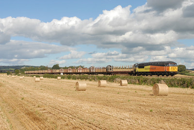 With baled straw in the foreground the 1st class 56 working on the logs  56094 on 6Z52 1035 Gloucester Yard ~ Teigngrace via Heathfield, down Stoke Canon 1455