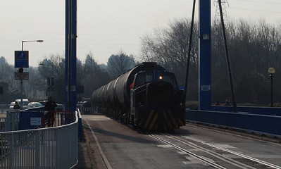 """From the exchange sidings the bitumen tanks are taken to the Total site by RIbble Rail. On 10th April this was done by """"Enterprise"""", a 1968 Rolls Royce diesel hydraulic, works number 10282. """"Enterprise"""" is seen here bringing 7 full bitumen tanks across the bridge on Navigation Way, a photo taken for the record due to the badly positioned sun."""