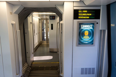 The vestibule between cars on the Acela Express.  Digital readouts advertise the next stop and final destination.  Unlike Germany's ICE trains, there is no digital readout of the train's speed.