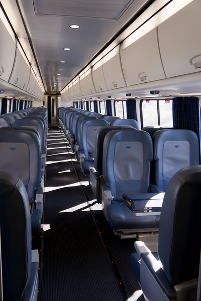 Inside a business class car on the Acela Express.  There is no coach class on this premium service, so these are the cheapest seats available.  There are no free snacks or newspapers, although several rows have the nifty fold-out tables.