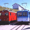 Red Rigi and Blue Rigi side by side at Rigi Klum.<br /> Blue Rigi powercar 12 & trailer 22 forming the 12:05 to Arth-Goldau stands next to red Rigi loco 18 forming a service to Vitznau. The Blue and Red Rigi railways were separate companies at one time but have retained the different liveries to the present day, 31/7/2012.