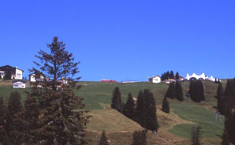 A view of the top of Rigi with a blue Rigi service descending to Arth-Goldau and a red Rigi service waiting to descend to Vitznau, 31/7/2012.