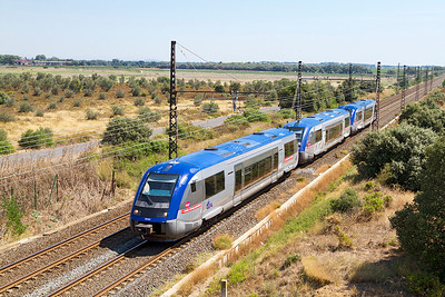 3 single car DMU's 73741, 73626 & 73740 in Conseil Regional Midi-Pyrenees livery head west past Beziers Airport. Sunday 18th August 2013.