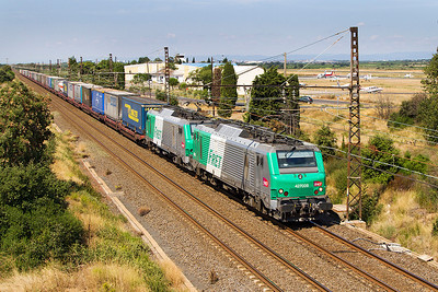 A pair of Alstom Prima dual voltage loco's 427028 & 427016 pass Beziers Airport with an eastbound intermodal working which originated in Spain. Sunday 18th August 2013.