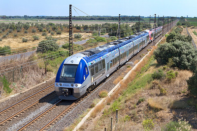Bi-Mode diesel/electric unit 81620 in Provence-Alpes-Cote d'Azur Norte Region livery with EMU 27661 in Languedoc-Roussillon livery form a stopping service to Narbonne westbound past Beziers Airport. Sunday 18th August 2013.