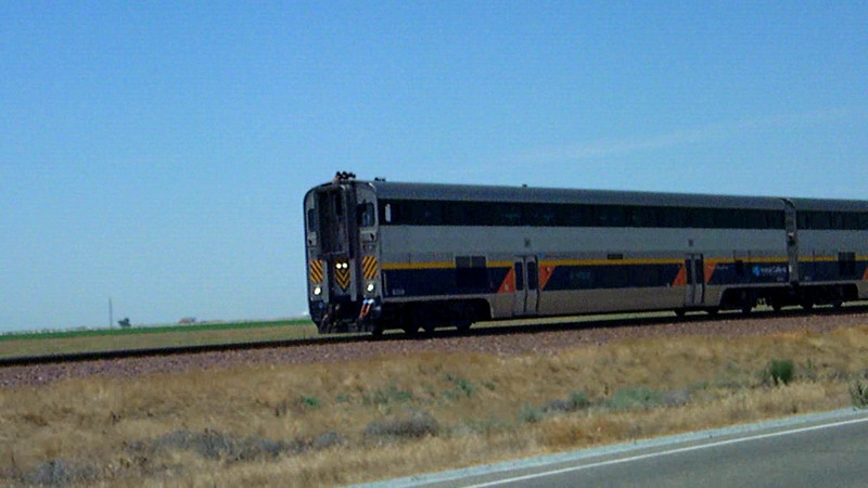 San Joaquin train 712 at speed next to highway 43, pushing south between Hanford and Corcoran in California's Central Valley.