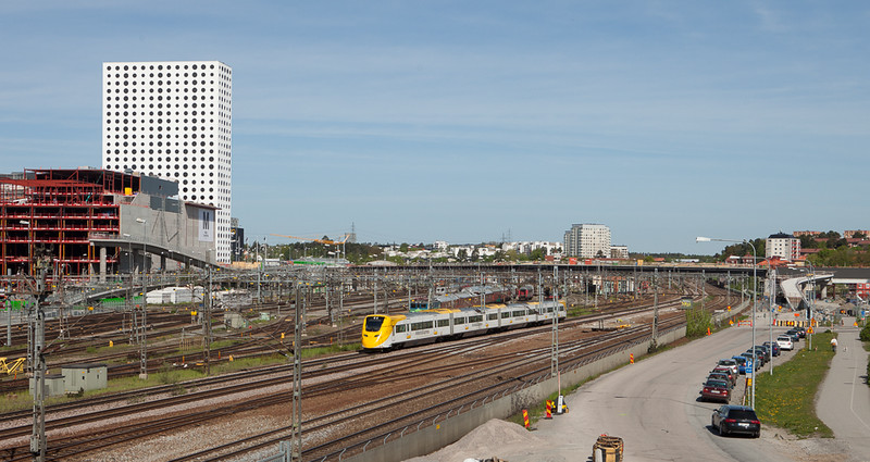 Arlanda Express in Solna passing the construction site of the Mall of Scandinavia.