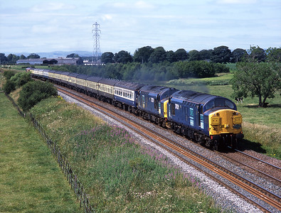 A returning charter from Glasgow-Birmingham International passes Greenlea near Dumfries with 37029 + 37229 on the front and 66045 on the rear, 16/7/05.