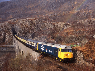 "With a hint of rainbow 50031 ""Hood"" hauls the Mallaig-Fort William leg of a  weekend tour from Swindon over Nan Uamh viaduct 5/3/05."