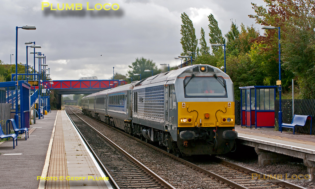 "67015 ""David J. Lloyd"" is working 5E00, 09:33 from Wembley Depot to Doncaster Wabtec, with a set of five Mk.3 coaches, presumably to be fitted with plug doors. The leading coach is RFM (GFW) 10208 which is carrying the Chiltern Mainline branding, followed by two silver TSOs without Mainline branding and two further TSOs in InterCity blue/grey livery. The train does not include a DVT. In order to allow other service trains to overtake it, the train was held in the new through line at Princes Risborough for a while and may well have been the first northbound train to use this line. It is seen passing through Haddenham & Thame Parkway station at 10:49, Tuesday 13th September 2011. Digital Image No. GMPI10282."