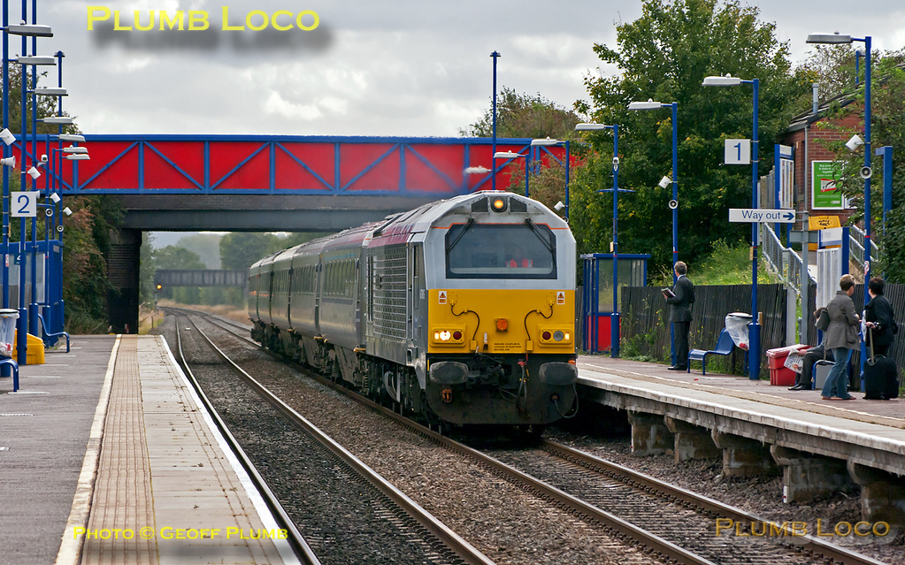 """67015 """"David J. Lloyd"""" is working 5E00, 09:33 from Wembley Depot to Doncaster Wabtec, with a set of five Mk.3 coaches, presumably to be fitted with plug doors. The leading coach is RFM (GFW) 10208 which is carrying the Chiltern Mainline branding, followed by two silver TSOs without Mainline branding and two further TSOs in InterCity blue/grey livery. The train does not include a DVT. In order to allow other service trains to overtake it, the train was held in the new through line at Princes Risborough for a while and may well have been the first northbound train to use this line. It is seen passing through Haddenham & Thame Parkway station at 10:49, Tuesday 13th September 2011. Digital Image No. GMPI10279."""