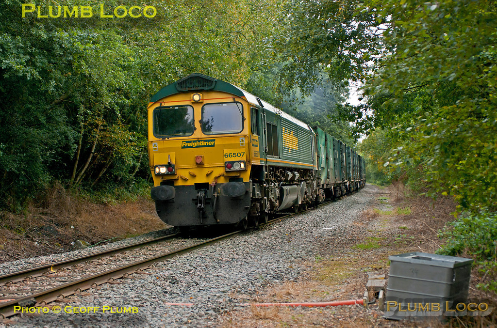 """Freightliner 66507 is still working hard as it runs through Sheephouse Woods on the final stretch into Calvert on the former Great Central main line. It is at the head of 6M22, the 08:21 from Cricklewood loaded """"binliner"""" train, which unusually, had 66544 dead on the rear. 13:10, Friday 21st September 2012. Photo taken from a public footpath across the line. Digital Image No. GMPI12492."""